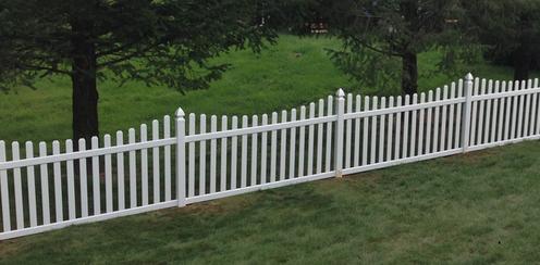 Malý zahradní dřevěný plot, natřený na bílo.