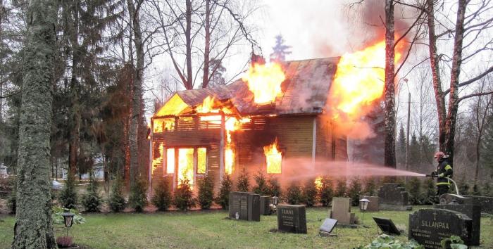 Dům v plamenech a hasí jej hasič